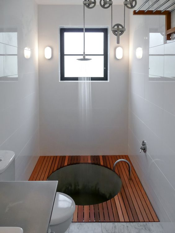 A pulley system adjusts the shower height above a sunken for How to build a sunken bathtub