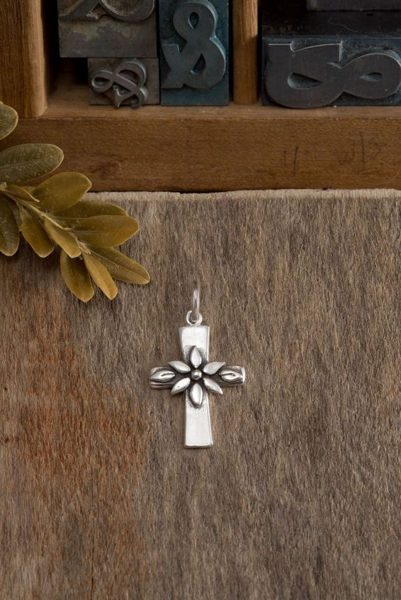 "Sterling silver cross adorned with blooming flower represents new life in Christ. Pendant measures approximately 1""x 5/8"" All sterling silver..."