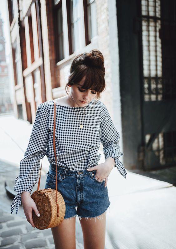 Camisa xadrez com laço nas mangas, short jeans, bolsa de palha