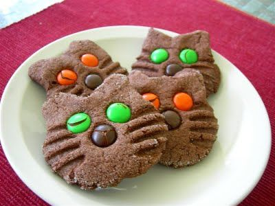 """Halloween Cat Cookies    1 box chocolate cake mix  1 c. peanut butter  1/3 c. water  2 eggs  M candies  Preheat oven to 375F. In large bowl beat peanut butter, water, and eggs. Gradually add dry cake mix. Roll into 1"""" balls and place on ungreased cookie sheet. Flatten each ball with bottom of glass dipped in sugar. Pinch out 2 ears at the top of each cookie. Press fork on both sides of face to form whiskers. Add M for eyes and nose. Bake for 8-10 minutes."""