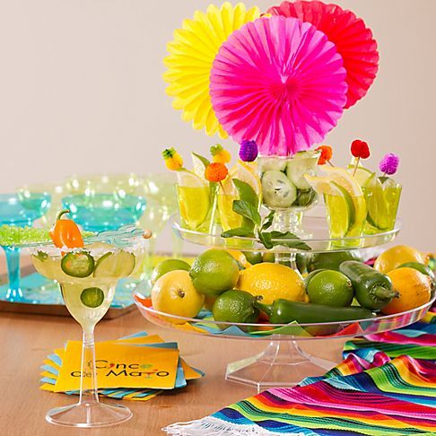 Make a magnifico margarita station by displaying garnishes in shot glasses on stacked cake stands.: