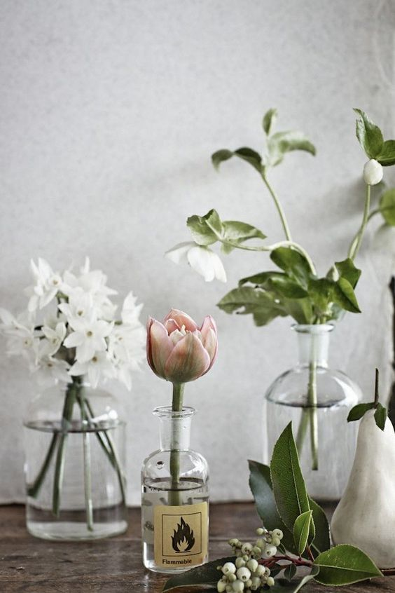 single flowers and touches of greenery in mismatched bottles: