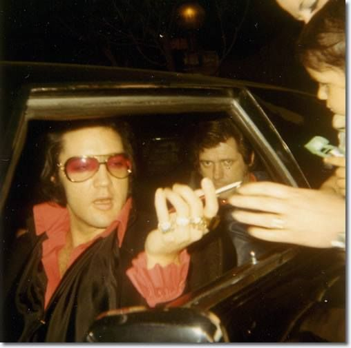 Monday, April 12, 1971: Elvis with Priscilla in the passenger seat and Charlie Hodge in the back seat of a car meeting fans outside his home at 1174 Hillcrest Road in Beverly Hills, California