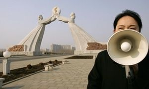 A North Korean tour guide talks in front of the Reunification Monument in Pyongyang in 2005.