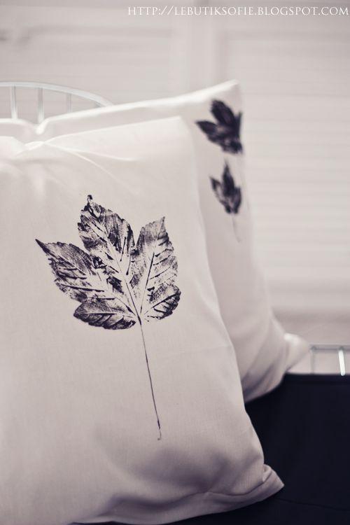 Die Kissen mit einem Bogen Zeitungspapier füllen, damit die Farbe nicht durchsickert. Schwarze Textilfarbe auf die Blätter-Rückseite auftragen und die Blätter auf das Kissen legen. Ein sauberes Zeitungspapier obendrauf drücken und glatt streichen. Blatt vorsichtig entfernen...Fertig!