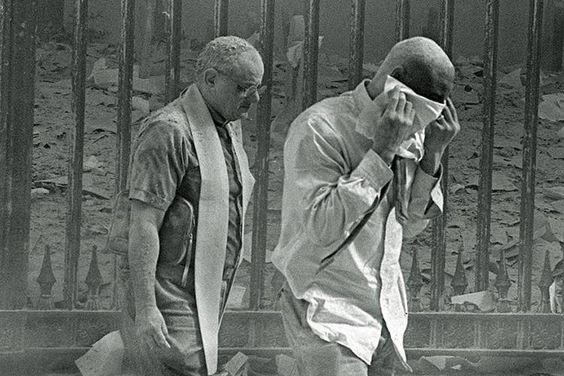 Homens cobertos de poeira caminham próximos ao local do atentado terrorista ao World Trade Center, na Ilha de Manhattan, em Nova York. Na manhã do dia 11 de setembro de 2001, dois aviões comerciais foram sequestrados no Aeroporto de Boston por terroristas da Al Qaeda, e instantes depois atingiram intencionalmente as duas torres do maior complexo comercial do planeta