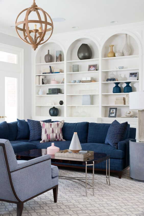 Navy blue sectional sofa and white built-in bookshelves in lovely family room. Blue and White Classic Decor Inspiration: Ella Scott Design. #blueandwhite #classicdecor #interiordesignideas #interiordesigninspiration #traditionalstyle