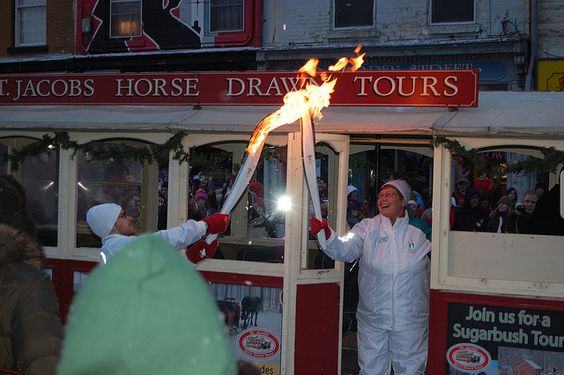The Olympic flame is passed on as the early morning crowd sings O Canada in downtown Guelph.