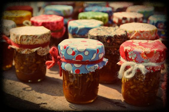 Our wedding gifts for guests. Delicious Homemade apple caramel jam with fabric mason jar covers. Each mason jar has a different fabric cover.  Tied with a piece of yarn. Made by White Hills Quilts.