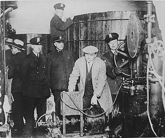 Detroit police inspecting equipment found in a clandestine underground brewery during the Prohibition era.