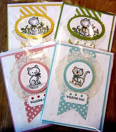 Maria's baby cards using Pretty Kitty, And Many More, Delicate White Doilies, Ticket Punch, & Sparkle embossing folder - all from Stampin' Up!