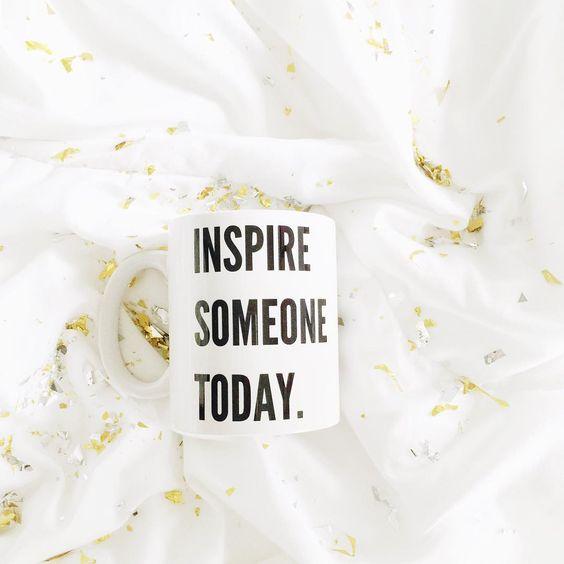 Caneca com a frase inspire someone today em cima da cama com confeitos dourados.: