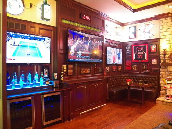 Family Room made into a Sports Bar w/multiple TV's, bar 2 fridges & Stadium style recliner seats along with sports memorabilia.