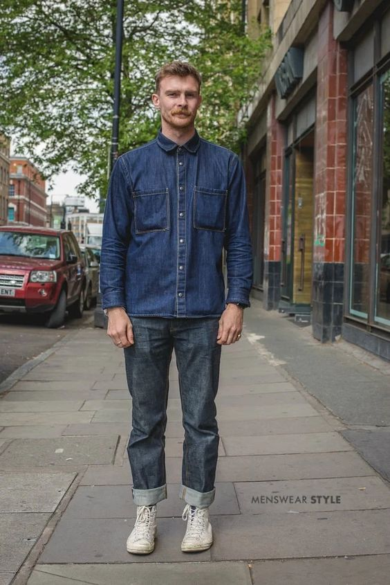 This is Harry on the streets of London in 2019 wearing White Canvas High Top Trainers, Selvage Denim Jeans, and a Denim Shirt.