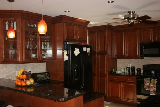 maple kraftmaid cabinets with a chestnut glaze, black and rust colored