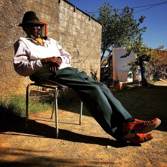 An old man known as Mtshuleni smokes his pipe whilst basking in the sun in Cradock, Eastern Cape.""