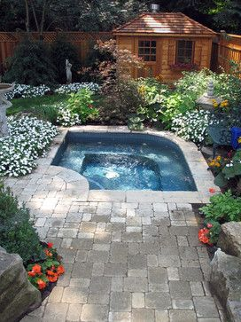 inground hot tub with pavers for the deck and landscaping as a privacy screen.