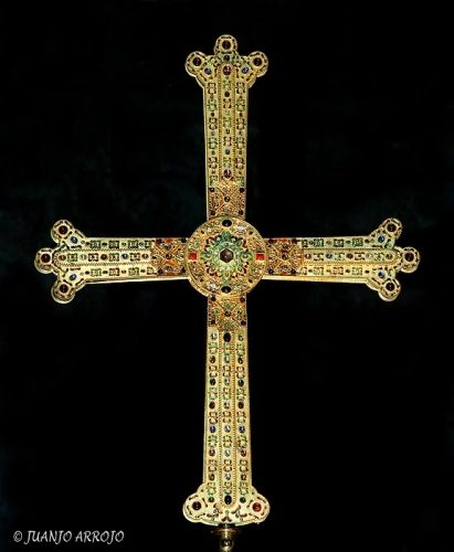 "The Victory Cross is a Prerromanesque jewel, symbol of Asturias.  Latin cross, oak wooden core coated with gold and precious stones. His arms are flared at the ends and a small shrine in the center of union.  It was made during the reign of Alfonso III, who ordered its production in the early tenth century as a donation to the Cathedral of San Salvador de Oviedo, as indicated on the back of the cross, along with enrollment in Latin ""HOC SIGN TVETVR IDLH. HOC SIGN VINCITVR INMICVS""."