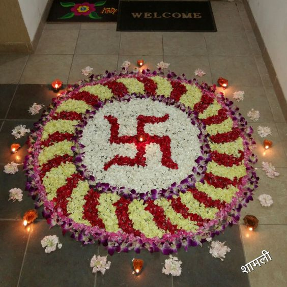 Flower Rangoli for festivals decorated with diyas  Swastik design