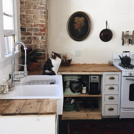 rustic kitchen with open shelving under butcher block counter tops. ikea farmhouse sink