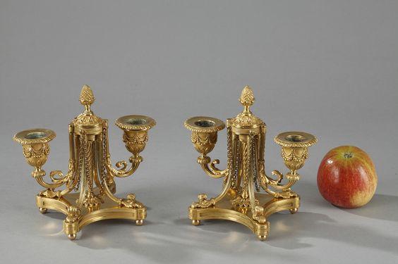 Paire de petits bougeoirs bouts de table d'époque Napoléon III, en bronze doré à deux bras de lumière soutenus par un axe central torsadé, renforcé par quatre consoles cannelées et feuillagées, reposant sur une base carrée à bords convexes et quatre pieds boules. Les bras de lumière, également cannelés, sont décorés de feuillages et les bobèches sont finement ciselées de rangs de perles et de feuilles d'eau. L'ensemble est surmonté d'une pomme de pin. Très belle qualité de la ciselure.