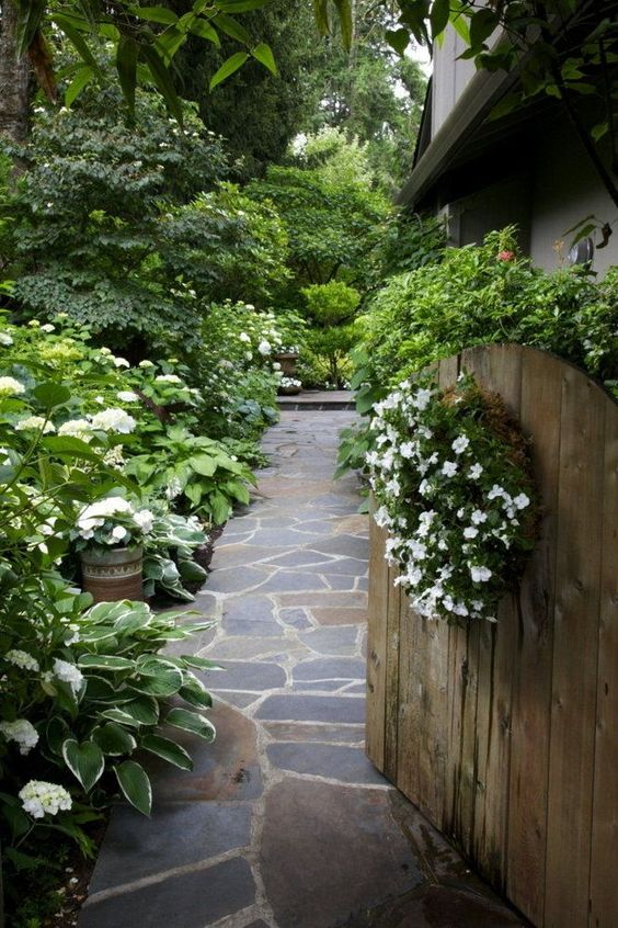 Garden gate ideas: a simple rustic wood arched garden gate opens to a lushly planted path for a romantic cottage style mood. #gardengate #secretgarden #cottagestyle #gardenideas #hosta