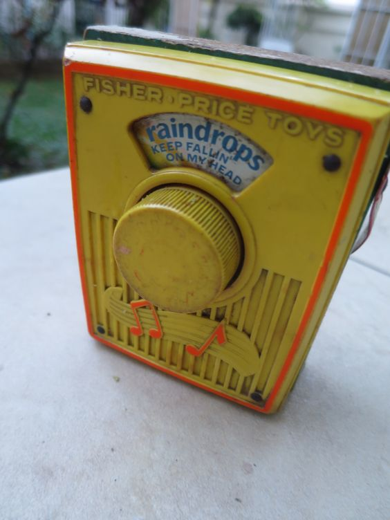 "Pocket Radio Music Box from Fisher Price - 1970's  It plays ""Raindrops Keep Fallin' on My Head"" as pictures of a little boy playing in the rain revolve past the ""screen"" on the front of the music box."