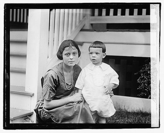 [Unidentified woman and child in front of porch]