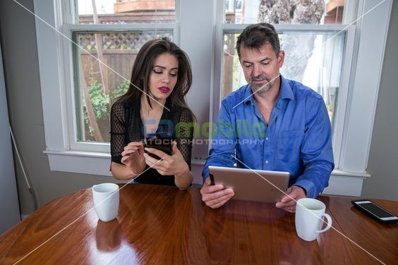 Urban couple, a man and a woman sitting at the breakfast table working with PC tablet and smartphone to search real estate listings and homes…