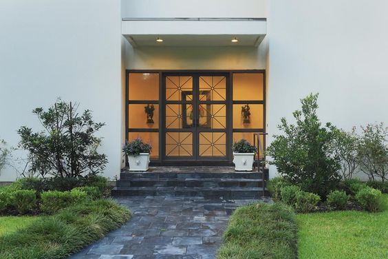 Slate walkway surrounded by lavish landscaping leads you to fine custom stately double glass and iron doors.