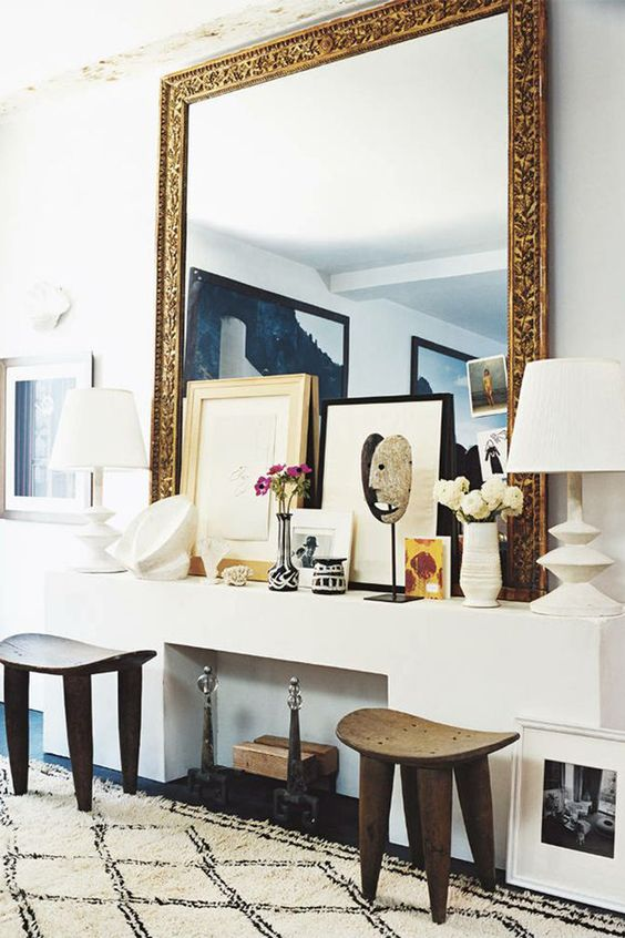 Make a gilded mirror the center of attention, stacking a few smaller art pieces in front of it for a layered look. Via Domino.   - HarpersBAZAAR.com: