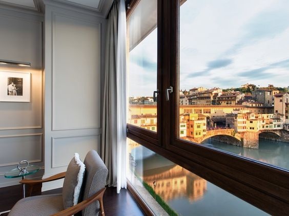 """If you're fantasizing about a romantic escape to Italy, it doesn't get much better than this. Owned by the Ferragamo family, the Portrait Firenze has 37 impeccably styled rooms and suites, all done in a sumptuous soft gray color palette. The one with the biggest """"wow"""" factor, however, is the Prestige Suite, which features sprawling views of the Arno river from both the bedroom and the living room."""