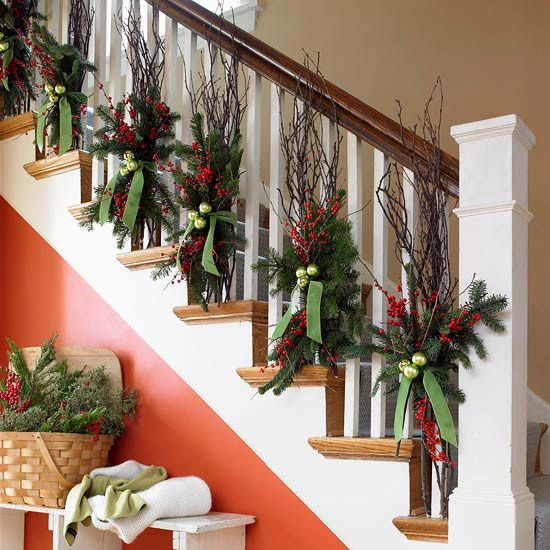 Add Height to Your Staircase: tie bundles of bare tree and winterberry branches to spindles for autumn look.  After Thanksgiving, tie pin boughs to the branches w/ velvet ribbon and wire Christmas ornaments around the ribbon.