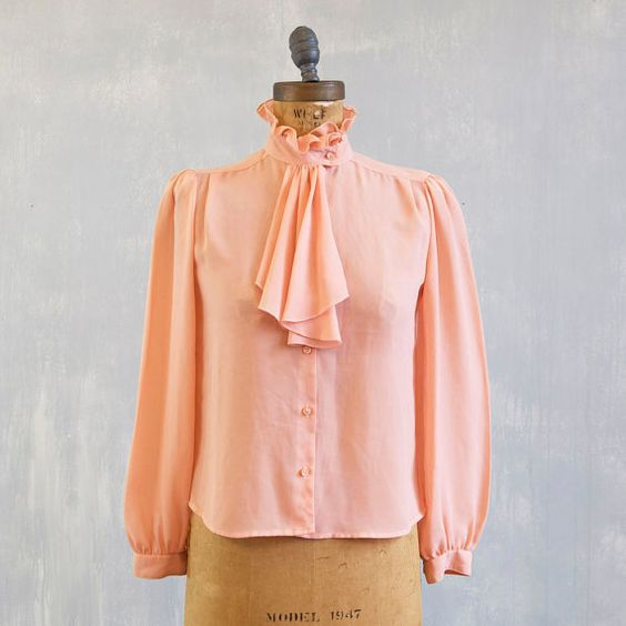 Beautiful color this secretary blouse with button down with pearl buttons a high ruffled collar and additional draped ruffles across the front.