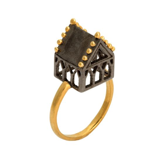 Part of the Hoyz ring collection, this exquisite piece features the Sanctuary design in oxidized silver with gold plate. The ring is a beautiful statement piece of jewellery, designed to be worn. Combining historical origins with contemporary style, these updated designs strike a perfect balance of new yet old. Inspired by antique Jewish wedding rings, the architectural symbol traditionally represented the marital home of the new couple. The detailed house or 'hoyz� in yiddish was a ...:
