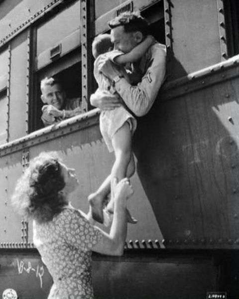 Wife of a departing soldier lifts her son for farewell embrace. Oklahoma, 1945: