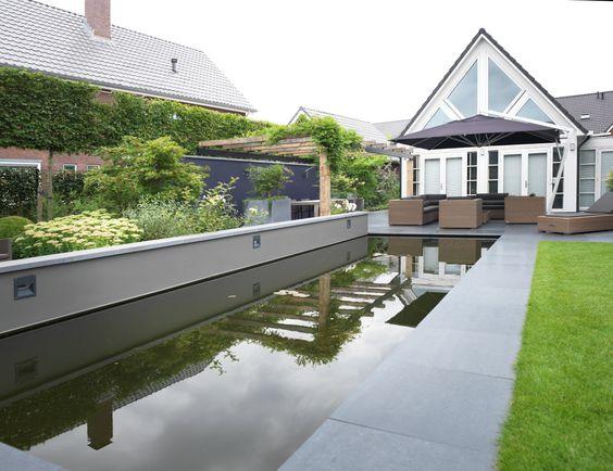 Moderne nieuwbouw tuin Elst. Elke woning moet voorzien zijn van een beetje groene oppervlak. Dit geeft ten eerste een levendig gevoel aan het huis en is het ook nog eens een bijdrage aan het totale oppervlak groen. Zo zie je op dit plaatje weer dat groen een zeer leuke sfeer kan toevoegen aan het huis. Zo ook het water!