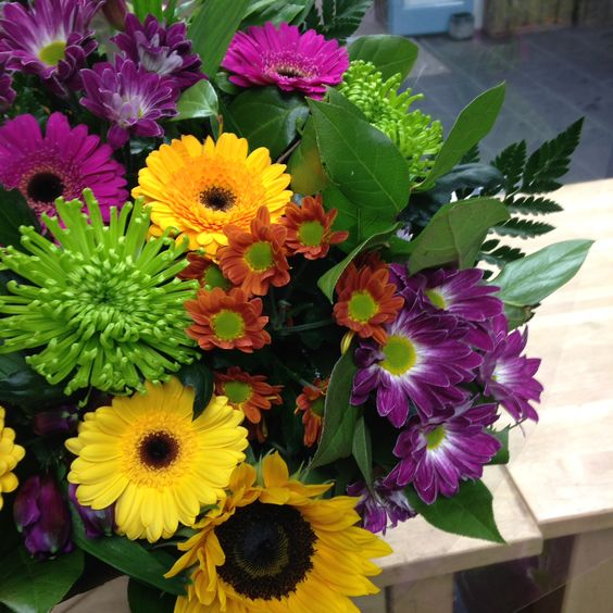 The brief: a colourful, cheerful bouquet. A celebration of life. A combination of yellow germini, green blooms, orange chrysanthemums, sunflowers and pink Chrysanthemums, I think it fits the bill.