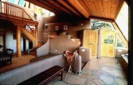 Inside an adobe earthship home in taos nm for Cost to build adobe home