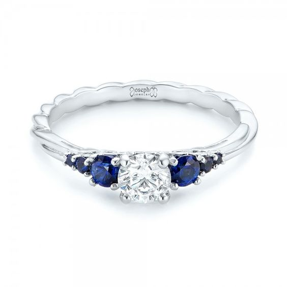 #103015 This beautiful engagement ring was custom designed for a client by Joseph Jewelry.This ring features a diamond prong set in the center with blue sapphires tapering down...