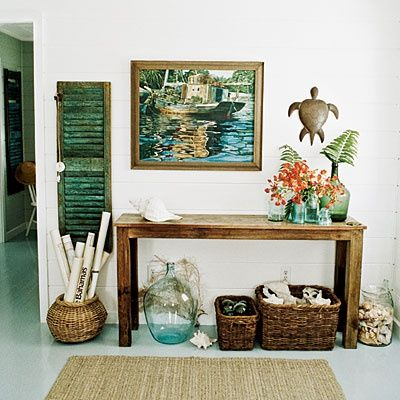 Make a welcome statement by grouping all of your beachy finds together at your entry: small seashells in a clear glass jar, conch shells in a large woven basket, and fishing floats in a smaller basket.: