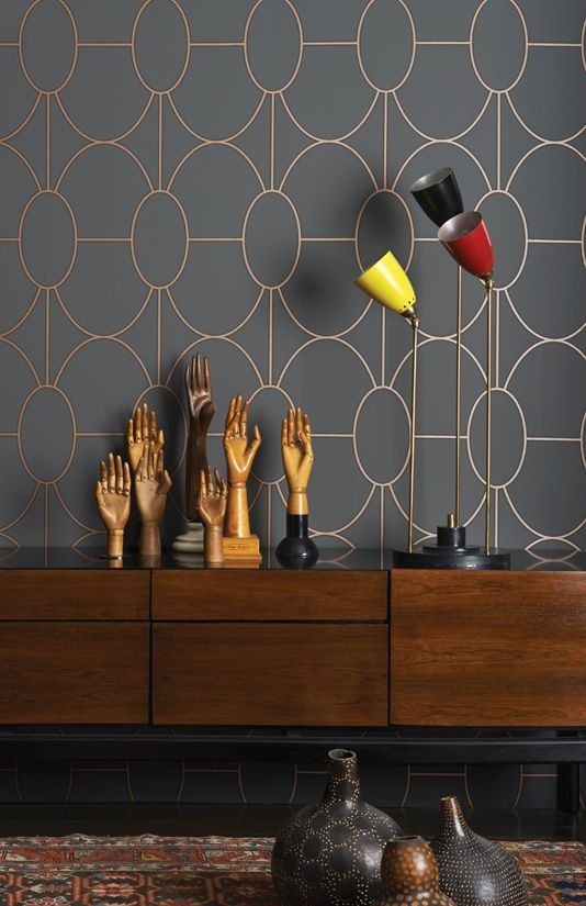 Riviera Wallpaper An elegant wallpaper that offers a softer and more graceful take on the geometry and linear styles of the Art Deco period. It features gently curved interlocking ovals printed with a softly raised textured finish, shown in metallic bronze on a charcoal grey ground.