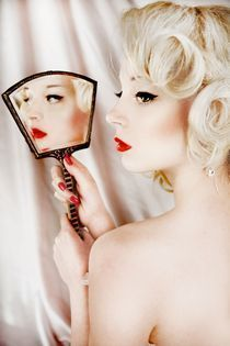 young woman with bare shoulders holding mirror by trigger image