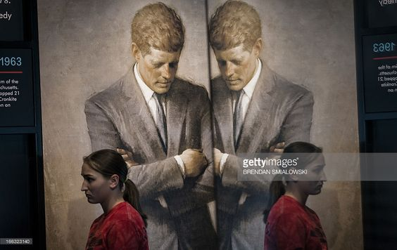 2013-11-14: A student walks past a copy of Aaron Shikler's official portrait of JFK which hangs in the White House. during a preview of an exhibit devoted to the assassinated US President John F. Kennedy at the Newseum in Washington, DC.