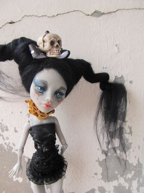 Monster High Ghoulia Yelps repaint. Ghoulia's been rerooted with black fluffy hair wrapped into pigtails, and repainted with blue eyes and drippy-looking eye makeup. She's wearing a golden neck ruff, a black tube dress, and a black bow with a skull in the center.