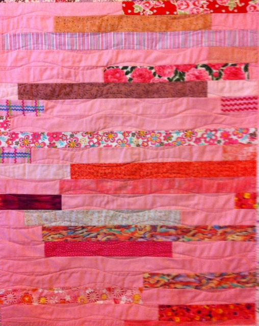 Pink Improv baby quilt using scraps and pink jelly roll style piecing