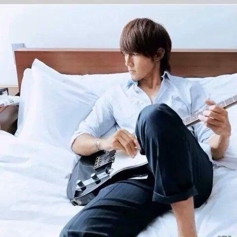 ベッドに座る稲葉浩志