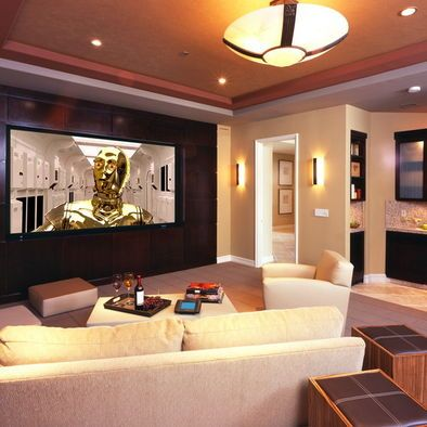 Love this dark wall behind the huge screen , the sconces on each side of the doorway, & wetbar off to side