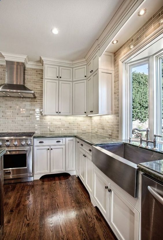 White kitchen cabinets with brick backsplash; love the way they built in the lighting over the sink instead of a pendant
