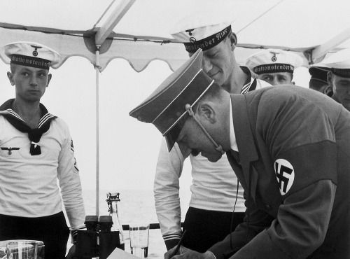 Hitler aboard the 'Nixe' on the terrain of the Olympic sailing regatta on the Kiel Fjord, writing autographs for the crew of the vessel - 11.08.1936